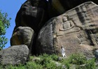 This photo taken on April 26, 2018, shows a Pakistani visitor walking past a seventh-century rock sculpture of a seated Buddha carved into a mountain in Jahanabad town in the northwestern Swat Valley of Pakistan, following a restoration process conducted by Italian archaeologists after the Taliban defaced it in 2007. The Buddha of Swat, carved on a cliff in the seventh century, was dynamited by the Pakistani Taliban in 2007. Now it has been restored, a powerful symbol of tolerance in the traumatised Pakistani valley. AFP photo