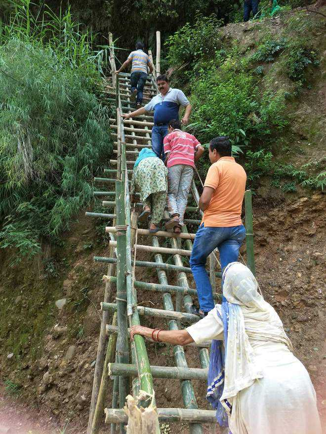 Road washed away, villagers build staircase  to reach home