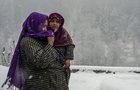A woman walks with her child at a village covered with a white blanket of snow after snowfall at Gagangir in Ganderbal district of central Kashmir, January 2, 2019. PTI
