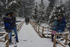 A tourist family enjoys during fresh snowfall at Gagangir in Ganderbal district of central Kashmir, January 2. PTI