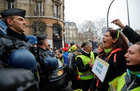 Protesters wearing yellow vests face police as they take part in a demonstration by the 'Women's yellow vests' movement in Paris, France, January 6. A placard reads: 'I am your daughter'. Reuters
