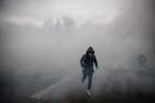 A demonstrator runs from a cloud of teargas in Paris on January 5, during an anti-government demonstration called by the yellow vest movement. AFP