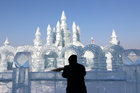 A cleaner sweeps the snow to prepare opening for pubic during the annual ice festival in Harbin, Heilongjiang province, China, January 7. Reuters