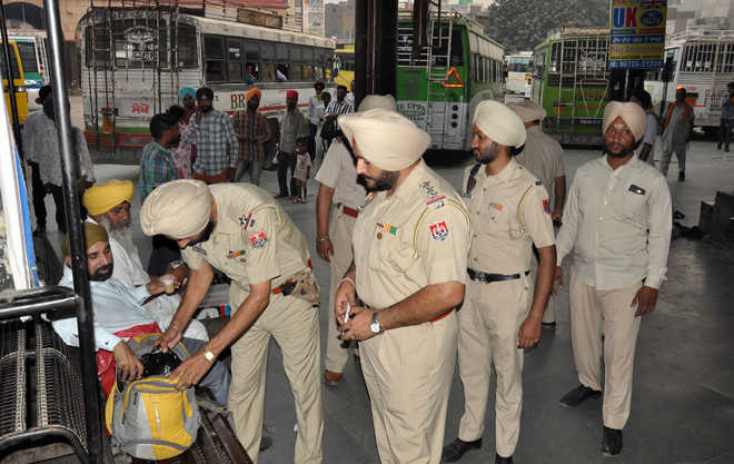 Police carry out security checks at city bus stand