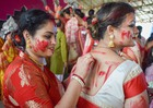 Bengali women smear vermilion or 'sindhoor' on each others' faces after worshipping the idol of the Hindu goddess Durga on the last day of the Durga Puja festival in Prayagraj on October 8, 2019. PTI photo