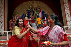 Bengali women smear vermilion or 'sindhoor' on each others' faces after worshipping the idol of the Hindu goddess Durga on the last day of the Durga Puja festival in Kolkata on October 8, 2019. Reuters