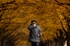 A woman walks under the trees with autumn coloured leaves in Moscow, Russia on October 8, 2019. — Reuters