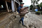 Residents remove muddy items from their flood-damaged home in Nagano on October 15, 2019, after Typhoon Hagibis hit Japan on October 12. — AFP
