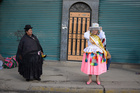 A traditional cholita observes her young daughter getting ready to dance at a preste celebration in La Paz, Bolivia. — Reuters