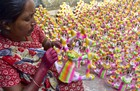 A woman colours a clay toy ahead of Diwali festival at Kumharpatti in Dhanbad district on October 18, 2019. — PTI