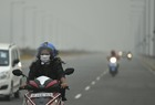 A woman wearing a pollution mask rides a scooter, in Ghaziabad on October 30, 2019. — PTI