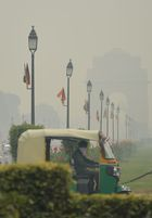 An auto rickshaw driver wears a mask as he drives past the India Gate monument amid thick air pollution in New Delhi on October 30, 2019. — AFP