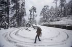 A person walks on a road connected to the Jammu & Kashmir Highway after fresh snowfall in Patnitop on November 8, 2019. PTI photo