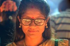 Fire light is reflected on the glasses of a devotee as she performs a ritual by lighting diyas (earthen lamps) on the occasion of Karthika or Kartik month in Hyderabad, on November 12, 2019. — AFP