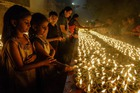 Young devotees perform a ritual by lighting diyas on the occasion of Karthika or Kartik month in Hyderabad, on November 12, 2019. — AFP