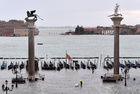 A person stands at the flooded St. Marks Square, as high tide reaches peak, in Venice on November 15, 2019. — Reuters