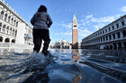 A woman walks at the flooded St. Marks Square during a period of seasonal high water in Venice on November 14, 2019. — Reuters
