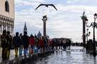 People walk on a footbridge across the flooded St. Marks Square by the statue of the Lion of St. Mark (L) and the Column of St. Theodore of Amasea (Rear R) on November 14, 2019 in Venice. — AFP
