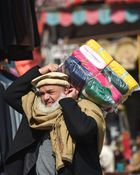 A Pakistani worker carries fabric bundles over his shoulder at a market in Rawalpindi on February 11. AFP