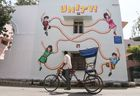 An Indian rickshaw driver looks at a mural at Lodhi Art District in New Delhi on March 24, 2019. — AFP
