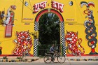 An Indian man rides his bicycle near a mural at Lodhi Art District in New Delhi on March 24, 2019. — AFP