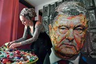 Ukrainian artist Daria Marchenko is pictured as she creates a large-scale artwork entitled 'The Face of Corruption' depicting the President Petro Poroshenko made with sweet wrappers of Roshen in Kiev, Ukraine March 27, 2019.— AFP