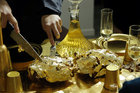 Artist and performer Frederique Lecerf carves a chicken covered with a thin sheet of gold as she prepares her performance meal for guests, a golden dinner with decadent 24 carat gold-covered dishes, in Paris, France, March 28, 2019. — Reuters