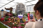 A visitor takes a photograph of a display entitled Floellas Future, by Baroness Floella Benjamin, during the 2019 RHS Chelsea Flower Show in London on May 20, 2019. — AFP