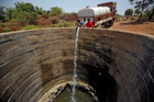 A dried-up well is refilled with water from a water tanker in Thane district in Maharashtra on May 30, 2019. Reuters