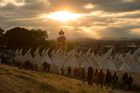 The sun sets as revellers look out from a viewing platform over the Tipi Village as they attend the Glastonbury Festival of Music and Performing Arts on Worthy Farm near the village of Pilton in Somerset, South West England, on June 26, 2019. — AFP