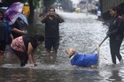 A man clicks photos of a girl playing with a dog on a waterlogged street during heavy monsoon rain at Sion in Mumbai, Tuesday, July 2, 2019. — PTI
