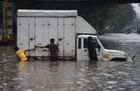 Indian men push a truck along a flooded street after heavy rain showers in Mumbai, July 1, 2019. — AFP