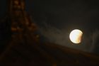 The moon is seen past the roof of a Hindu temple at Basantapur Durbar square during a partial lunar eclipse in Kathmandu on July 17, 2019. — AFP