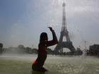 A woman cools off at the Trocadero Fountains next to the Eiffel Tower in Paris, on July 25, 2019 as a new heat wave hits Europe. AFP