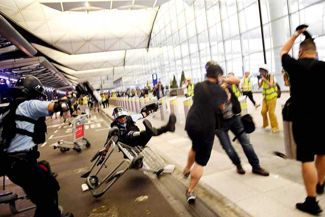 Police use pepper spray in scuffles with protesters at Hong Kong airport