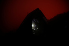The red glow of the lava lake is seen as a Virunga park employee sits in a shelter on the edge of Nyiragongo volcanos crater inside the Virunga National Park near the eastern Congolese city of Goma in the Democratic Republic of Congo, August 9, 2019. — Reuters