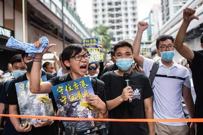 HK protesters boo Chinese anthem, as leader warns against interference