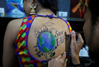 An artist applies final touches to a body paint tattoo sketched on the back of a woman in preparations for the upcoming Navratri in Ahmedabad on September 24, 2019. — Reuters